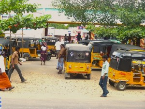 Woman in bus stand, autos
