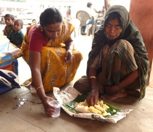 Woman in the bus stand, feeding