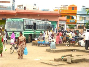 woman in bus stand, green bus